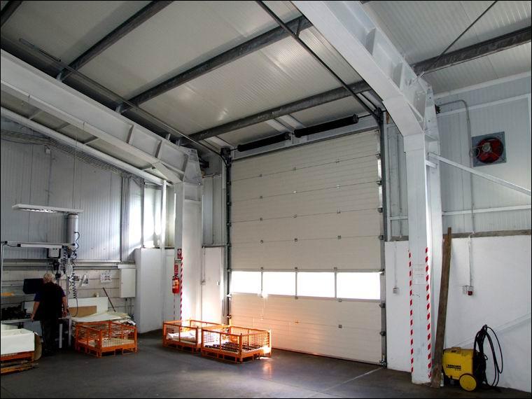 Szekcionált, panoráma ablakos ipari kapu belülről, tetőkövető sínvezetéssel